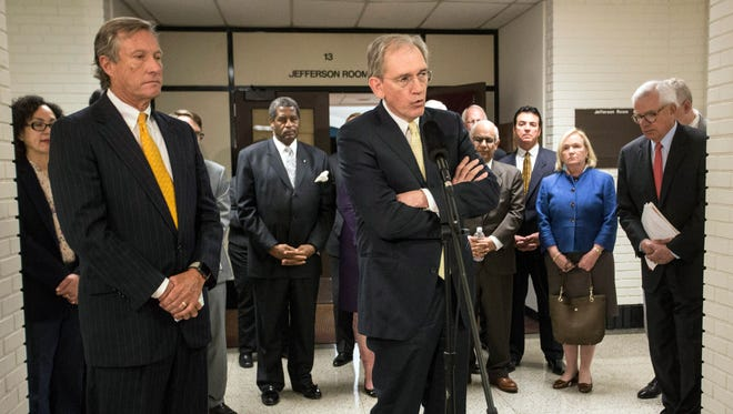Flanked by the University of Louisville board of trustees and foundation members, legal counsel Andy Campbell answers questions about a pending lawsuit against former university president Dr. James Ramsey after a private meeting and vote on Wednesday morning. 4/25/18
