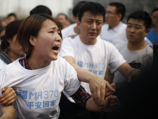 A relative of passengers on missing Malaysia Airlines flight MH370 yells at a security personnel while she attends a protest outside the Malaysian embassy in Beijing on March 25, 2014. Scores of angry relatives of the Chinese passengers aboard Flight MH370 set out on a protest march to the Malaysian embassy in Beijing on March 25 to demand more answers about the crashed plane's fate.
