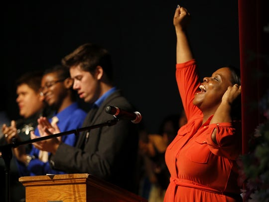 Anika Daughtry, cousin of Rod Durham, cheers during a celebratory moment for the life of Rod Durham at his memorial service Monday at Leon High School, from where he graduated in 1982 and later went on to teach drama classes.
