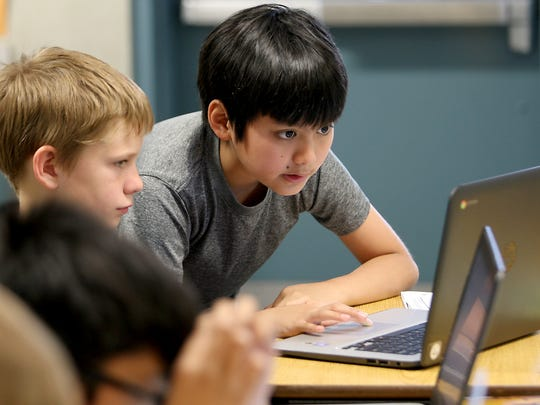 SWAT team member Ethan Jingco, 11, (right) helps fellow student Kaden Dunn, 11, with his computer during class at Emerald Heights Elementary School in Silverdale on Wednesday, May 10, 2017.