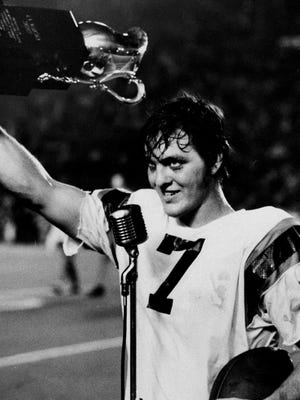 Florida quarterback John Reaves waves the trophy he won for being named Most Valuable Player in the 1971 Florida-Miami game.