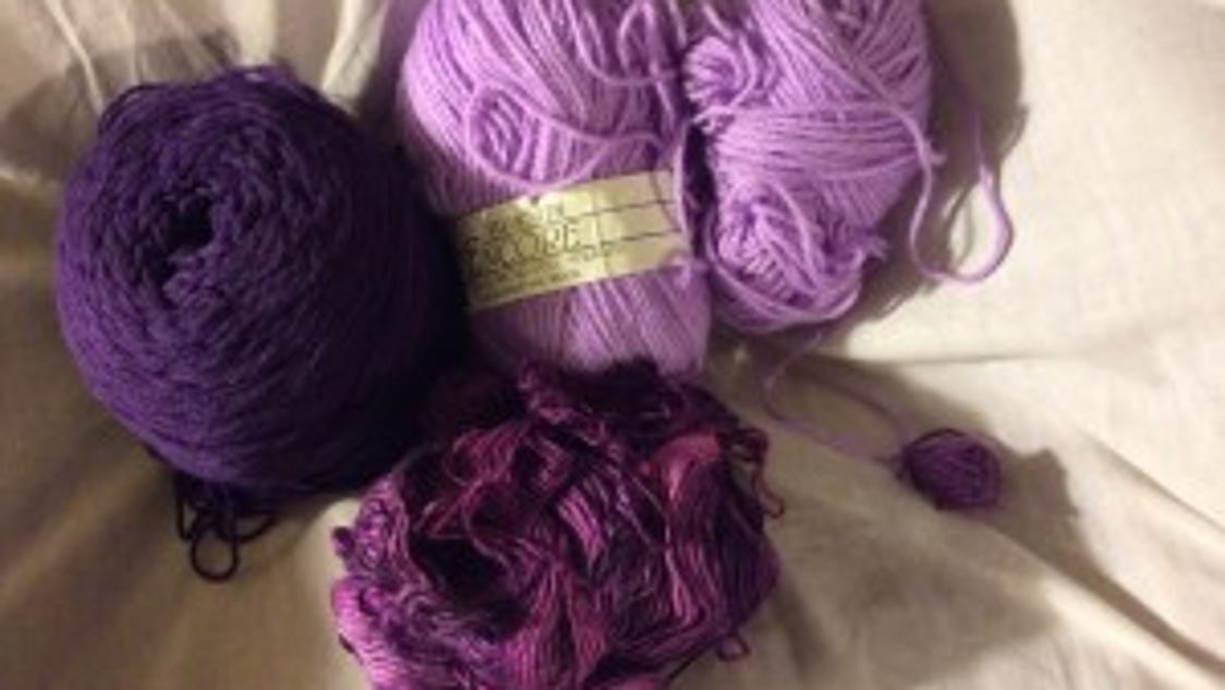 Knitting purple baby hats for shaken baby syndrome