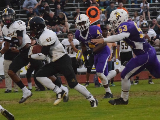 Leesville's Daquan Davis (27, far left) out distance ASH defenders Tyriq Reese (4) and Ke'Elijah Bell (53) on his way to score a touchdown.