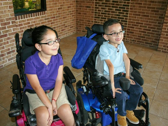 Anthony Castillo, Avalon Elementary School kindergarten student, right, and his sister Itzel Castillo, a first grader, wait patiently to board their adaptive bicycles in front of their school.