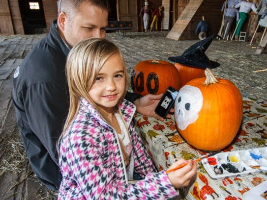 Fred and Avery Fischer, 8, of Merton decorate pumpkins