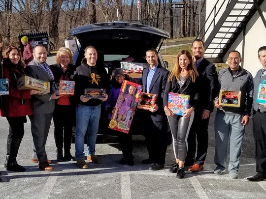 Zoey and Rich with Master Network Members with a car load of toys donated to Love Holds Life.