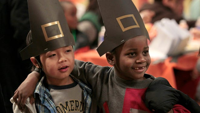 New best pals second grader Kae Doh Soe, a native of Thailand, and first grader Pierre Baraka, a native of the Republic of Congo, right, are all smiles and laughs as they walk through the crowded cafeteria sporting their pilgrim hats made in art class, at the Rochester International Academy's 5th annual Thanksgiving Dinner held at the school Monday, Nov. 23, 2015.   The event has gotten so big, the school held two separate seatings for their students and their families.