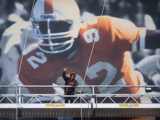 A crew member waves while taking down a photo of former Vols football player Reggie White from the video board at Neyland Stadium on Tuesday.