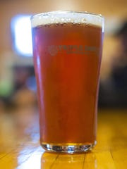 A glass of Pumpkin Hucker ale at Triple Dog Brewing