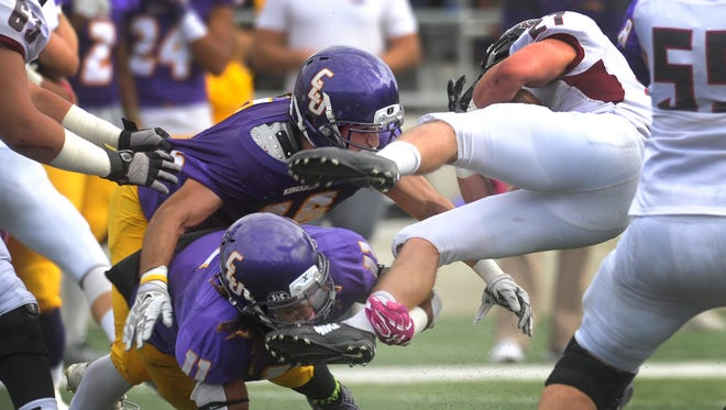 CLU's Trevor Roe(top) helps his teammate Acquarey Eddington take down Chapman's Joe Mudie in the seceond quarter of their homecoming game Saturday.