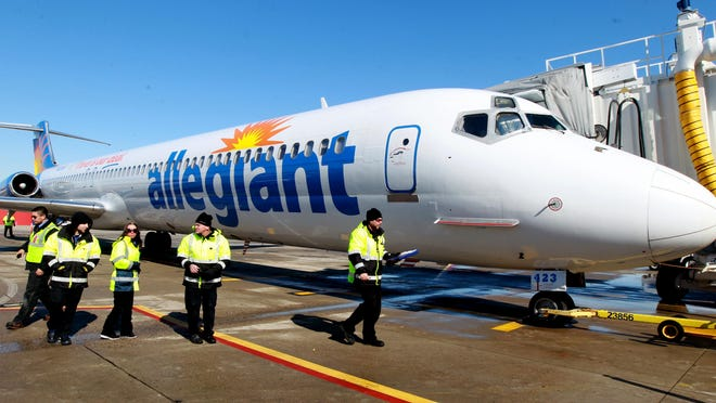 Ground crew members disperse after preparing an Allegiant Travel Company MD-82 jet for departure from Cincinnati/Northern Kentucky International Airport.