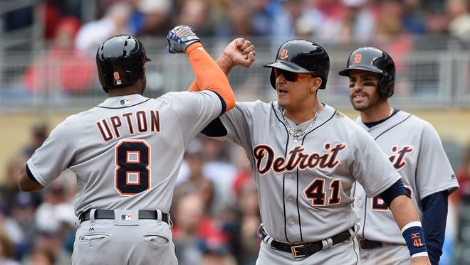 Victor Martinez #41 and J.D. Martinez #28 of the Detroit Tigers congratulate teammate Justin Upton #8 on a three-run home run against the Minnesota Twins during the first inning of the game on April 30, 2016 at Target Field in Minneapolis, Minnesota.