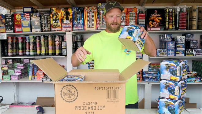 In this file photo, Travis Kowalski-King sells fireworks at the Boomtown Fireworks stand in East Bremerton. Operators of fireworks stand in unincorporated Kitsap County will be limited in what they can sell this year after county commissioners passed fireworks restrictions on Wednesday.