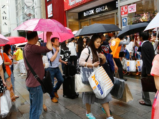 Chinese tourists with shopping bags wait for a sightseeing bus in front of a discount electronics store in Tokyo's Ginza district on June 17, 2015.