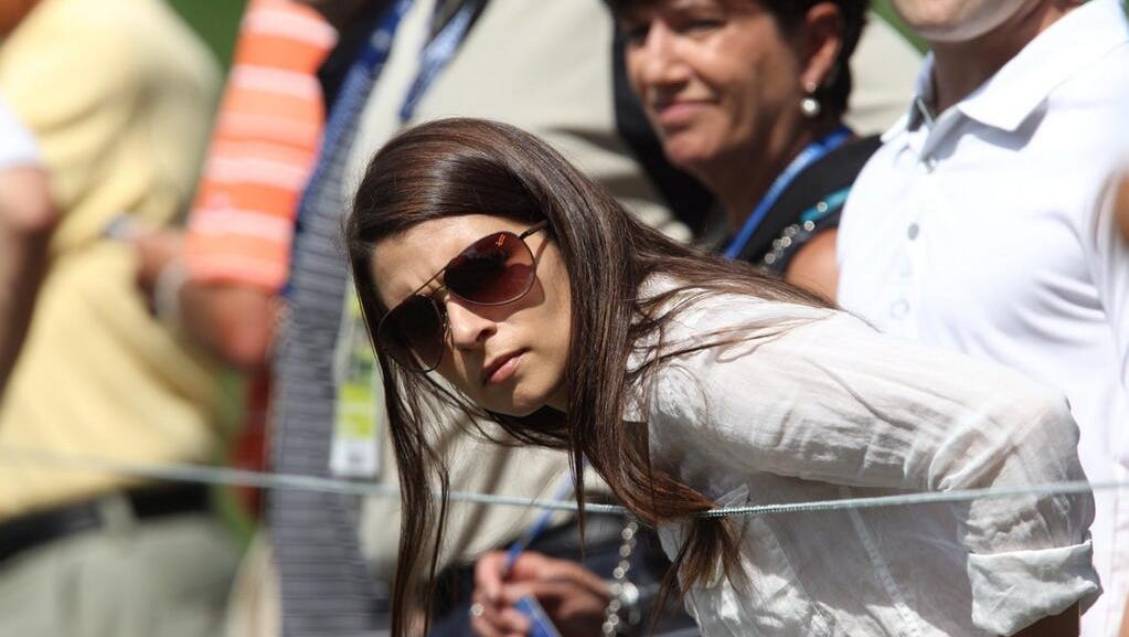 NASCAR's Danica Patrick watches Tigers Woods play the first hole.