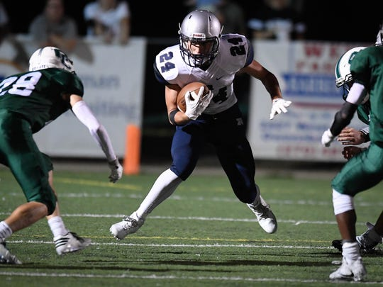Reitz's Andrew Word (24) runs against the Catholic