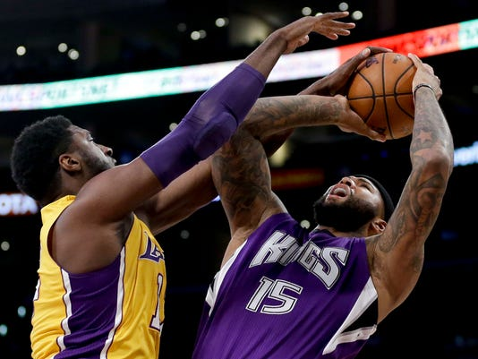 Los Angeles Lakers center Roy Hibbert, left, blocks a shot by Sacramento Kings center DeMarcus Cousins during the first half of an NBA basketball game in Los Angeles, Tuesday, March 15, 2016. (AP Photo/Chris Carlson)