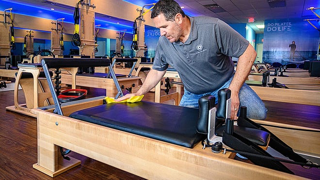 David Russo, co-owner of the Club Pilates franchise in St. Augustine, disinfects one of his workout machines on Tuesday. Russo, whose business reopened four weeks ago after being closed for two months, now sanitizes every machine after every use by his customers.
