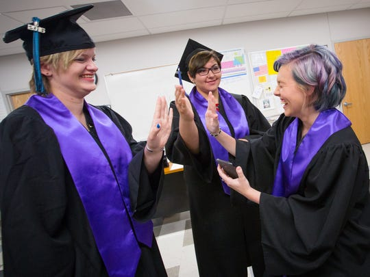 "Alma d'Arte Charter High School graduating students Layla Jackson, left, Stephanie Marta and Raini Schauer try to ""high-five"" one another before the start of commencement ceremonies at the Court Youth Center, May 26, 2016."