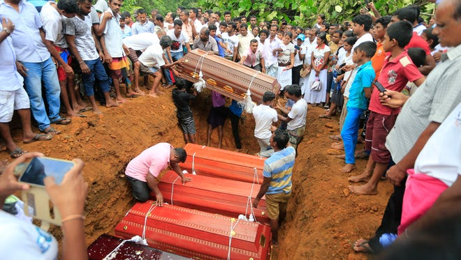 Sri Lankan villagers prepare to bury victims of a landslide at a cemetery in Bellana village, in Kalutara district in, Sri Lanka, Saturday, May 27, 2017. Sri Lanka has appealed for outside help as dozens were killed in floods and mudslides and dozens others went missing.