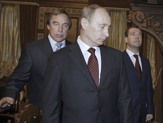 Russian cellist Sergei Roldugin, left, escorts then-Russian