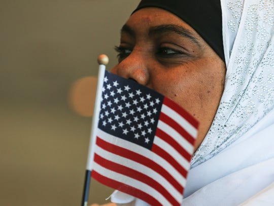 Zuiekha Khaleel holds a small American flag while waiting