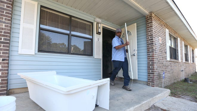 Maintenance workers Jerry Maul removes a bath tub from a home in the Orange Avenue Apartments on Tuesday, Nov. 1, 2016.