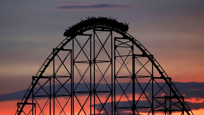 In this July 3, 2017, file photo people ride a roller coaster at dusk at the Worlds of Fun amusement park in Kansas City, Mo. You're still going to spend a lot of time waiting. If you're a local, you can bail when it gets too crazy and come back another day. If, however, this is a once-in-a-lifetime trip at a time when crowds will be thick, splurging on line-skipping passes could mean actually getting to enjoy all the attractions you came to see, says Robert Niles, editor of ThemeParkInsider.com. (AP Photo/Charlie Riedel, File)