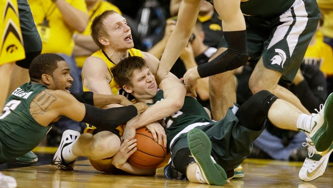 Iowa guard Mike Gesell, center, fights for the ball with Michigan State's Alvin Ellis III, left, and Matt McQuaid, right, during the first half of an NCAA college basketball game Tuesday in Iowa City, Iowa.