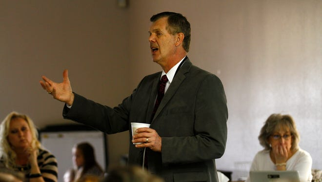 Farmington Municipal School District Superintendent Gene Schmidt addresses the crowd Thursday at district headquarters during a meeting about the possible creation of a family school program.