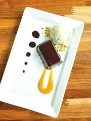 The flourless chocolate torte with a scoop of pistachio