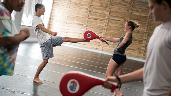 """Landen Warfield, 15, kicks a pad held by Lacey Watkins, 16 during a Hanover Area YMCA summer camp program called """"Leadership through Martial Arts."""" The 10 week self-defense course doubles as a program to teach kids leadership skills with a specialized focus on anti-bullying."""