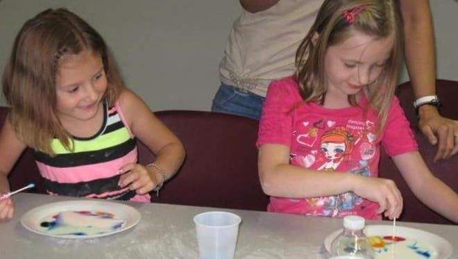 Izabell Potocki, left, and Aleah Weiglein, both of Brownsville, have fun with the color changing milk experiment at the Brownsville Public Library.