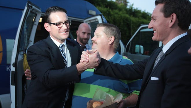 Riverside District Attorney challenger Mike Hestrin, left, is congratulated by deputy DA Daniel Delimon, right, and supporter Mike Anderson after the first numbers came in. Photo taken at during election night on Tuesday, June 3, 2014 at Anderson's home in Riverside.
