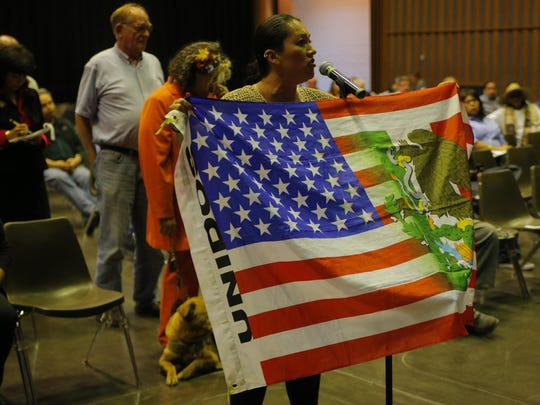 Ana Barrera holds a blended United States and Mexico flag as she speaks during a community listening session organized by the U.S. Department of Justice's Office of Community Oriented Policing Services on Tuesday at Sherwood Hall in Salinas.