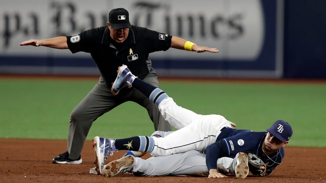 Tampa Bay Rays shortstop Willy Adames lands on top of Toronto Blue Jays' Jonathan Davis, bottom, after Davis stole second base during the sixth inning of a baseball game Saturday, Sept. 7, 2019, in St. Petersburg, Fla. Doug Eddings, top, makes the call. (AP Photo/Chris O'Meara)