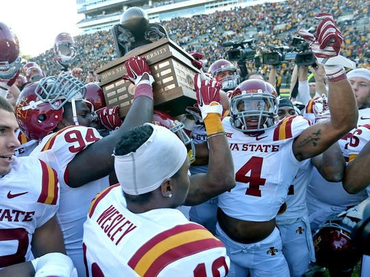 Iowa State players celebrate with the Cy-Hawk Trophy