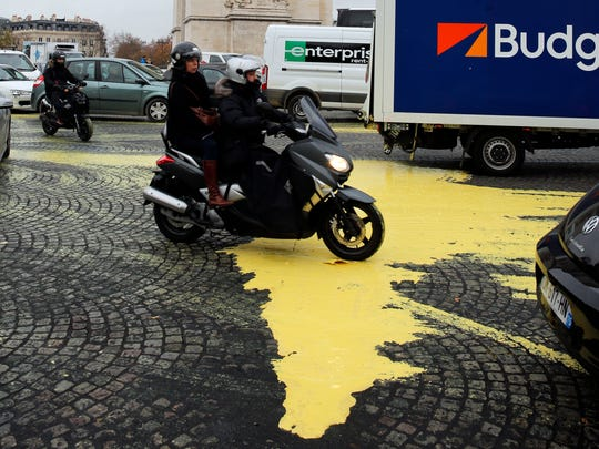 Yellow paint is poured on the street during a protest by activists from environmental group Greenpeace on the Champs-Elysee in Paris, Friday, Dec. 11, 2015 . The protest is one of many activist actions linked to the COP21, the United Nations Climate Change Conference. (AP Photo/Christophe Ena)