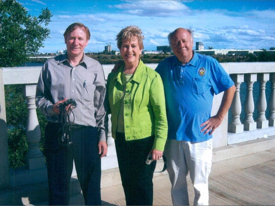 """Left to right, Jim Meinert, associate producer, and co-producers Norma Ashby and Craig Wirth, from the film documentary, """"The Great Falls Story,"""" stand on the 10th Street Bridge."""