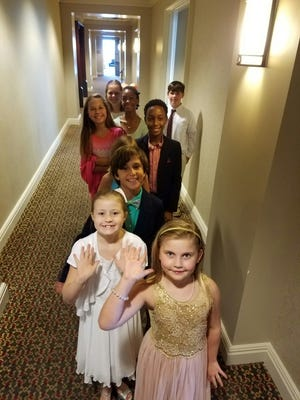 Excited, young etiquette class students lined up to enter the Skyline Ballroom for a graduation ceremony and dinner Thursday night at the Capital City Club.  Front to back: Abbie Roblee, Skyler Humphrey, Michael Matte, Campbell Baker, Kevin Taylor, II, Anna Nekic, Kendall Hardway, Mallory Matte, John Mark Andrews.