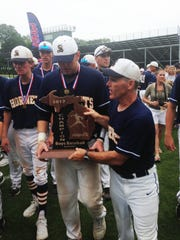 Coach Scott Theisen hands the Division 1 championship trophy to Sean O'Keefe.