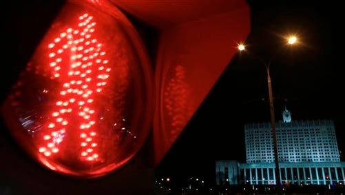"""A traffic light shows a red light, with the Russian government headquarters in the background, in Moscow, Tuesday, Jan. 13, 2015.  New Russian road safety regulations bar transsexuals, transvestites and others with sexual """"disorders"""" from driving."""