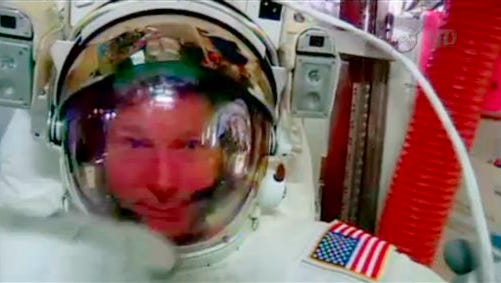 In this image made from video provided by NASA, astronaut Terry Virts points to his helmet as he sits inside the International Space Station on Wednesday, Feb. 25, 2015 during an inspection for water in his suit. Virts reported the water while he waited in the air lock for today's spacewalk to formally conclude.