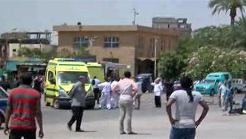 In this still image taken from video, security personnel and spectators gather at the scene of a suicide bombing just steps away from the ancient Egyptian temple of Karnak in the southern city of Luxor, Egypt, visited by millions of tourists every year, Wednesday, June 10, 2015. Shortly after the explosion, police exchanged fire with and killed two suspected Islamic militants who had arrived at the sprawling, Nile-side temple together with the suicide bomber,  security and health officials said. (AP Photo)