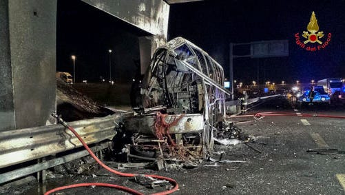 A firefighter sprays water on the burned hulk of a bus that crashed and burst into flames near Verona, northern Italy, Saturday, Jan. 21, 2017. Police say 16 people have died when the bus carrying Hungarian school students returning home from France crashed into the side of a highway near Verona. Thirty-nine people survived. The bus was returning to Budapest with students ages 15 to 17.