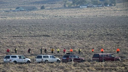 Officials comb the area where a plane crashed and the pilot died on the race course while attempting to qualify for the Reno National Championship Air Races in Reno, Nev., Monday. This is the same event where a wreck in 2011 killed a pilot and 10 spectators on the ground.