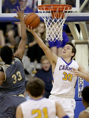 Carmel Greyhounds PJ Baron (30) attempts a shot but is blocked by Warren Central Warriors Ki-ng Tyler (33) in the second half of their game Friday, February 17, 2017, evening at Carmel High School.