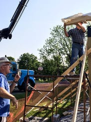 Phil Tipton, left, and the Rev. Alan Smith work to