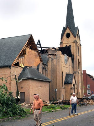 People walk past the very  heavily damaged First Baptist Church in Portland after severe storms Monday  6/22/2015.