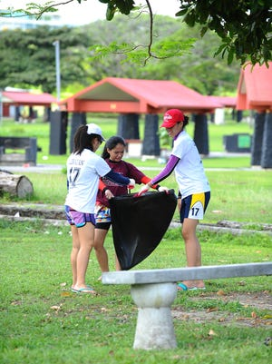 In this Oct. 28, 2015 file photo, student athletes from the Philippines' Assumption Antipolo school collect trash at Ypao Beach Park in Tumon.